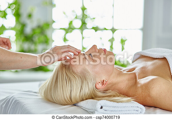 Beautiful woman with closed eyes getting a massage in the spa salon - csp74000719