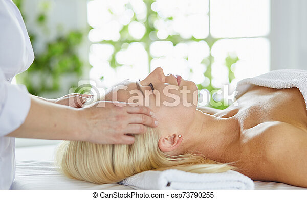 Beautiful woman with closed eyes getting a massage in the spa s - csp73790255
