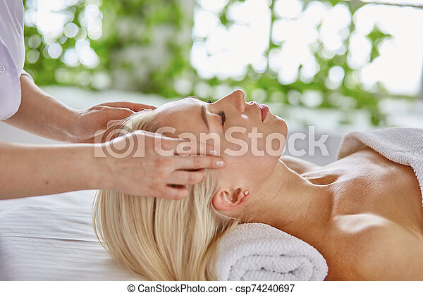 Beautiful woman with closed eyes getting a massage in the spa s - csp74240697