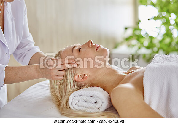 Beautiful woman with closed eyes getting a massage in the spa s - csp74240698