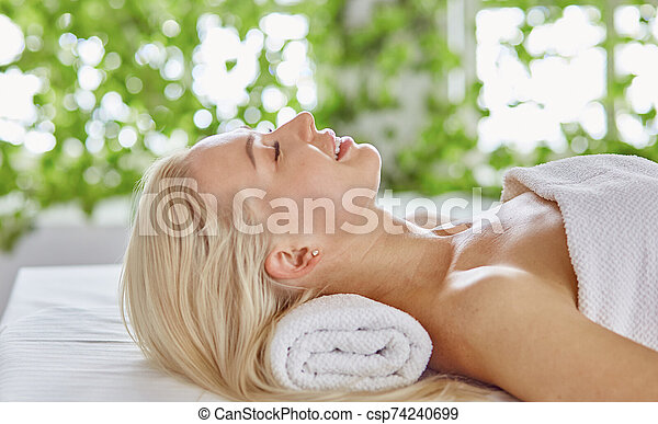 Beautiful woman with closed eyes getting a massage in the spa s - csp74240699