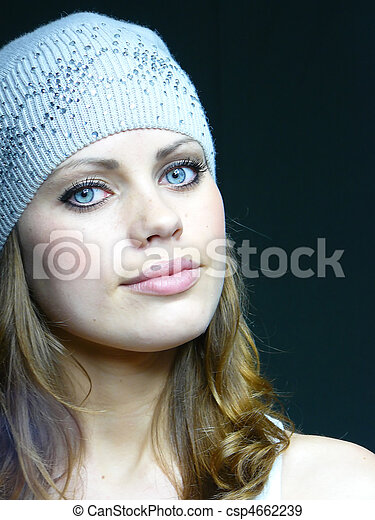 beautiful young blue-eyed woman in a grey cap with pastes - csp4662239