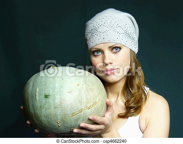 beautiful young blue-eyed woman with a pumpkin in hands - csp4662240