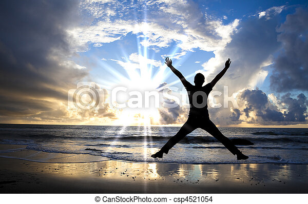 happy man jumping on the beach with beautiful sunrise - csp4521054