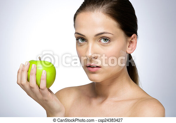 Portrait of a young beautiful woman with green apple - csp24383427