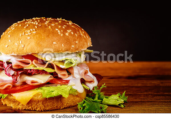 Sandwich with ham, lettuce, cheese and tomato. - csp85586430