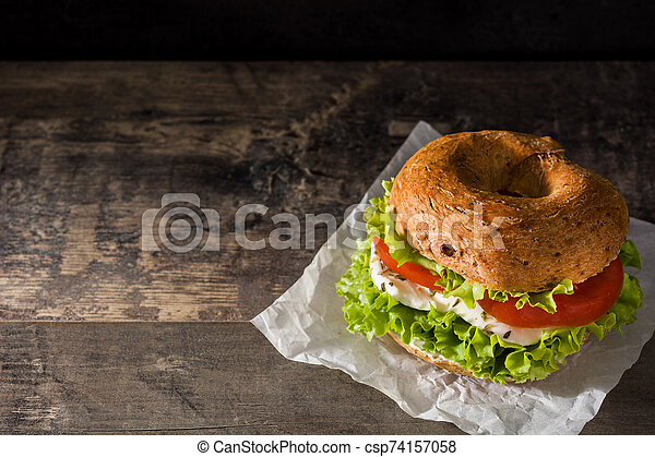 Vegetable bagel sandwich with tomato, lettuce, and mozzarella cheese on wooden table - csp74157058