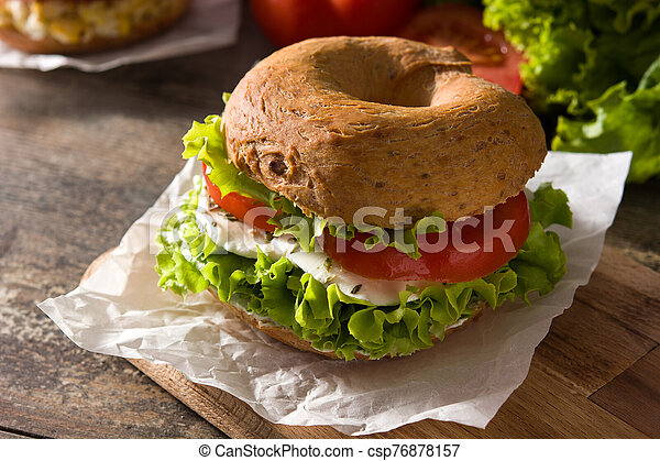 Vegetable bagel sandwich with tomato, lettuce, and mozzarella cheese on wooden table. - csp76878157