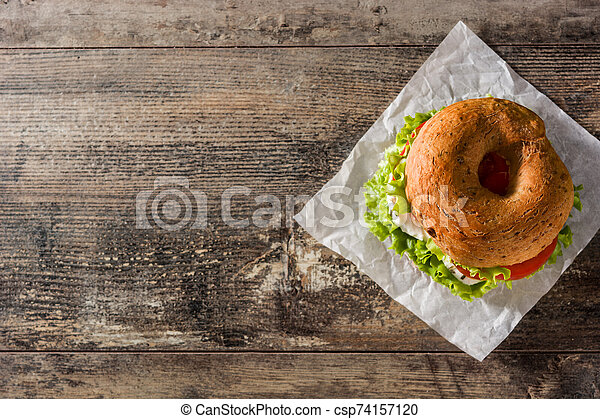 Vegetable bagel sandwich with tomato, lettuce, and mozzarella cheese on wooden table - csp74157120