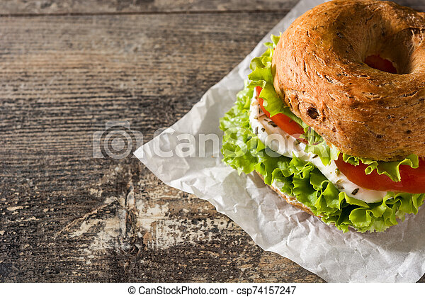 Vegetable bagel sandwich with tomato, lettuce, and mozzarella cheese on wooden table - csp74157247