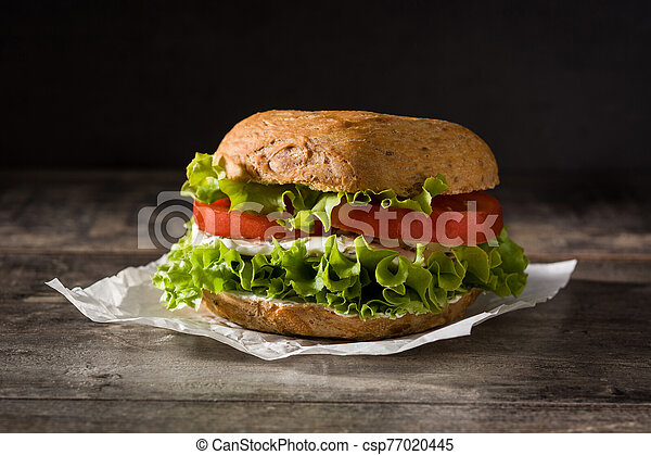 Vegetable bagel sandwich with tomato, lettuce, and mozzarella cheese on wooden table. - csp77020445