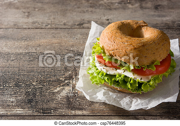 Vegetable bagel sandwich with tomato, lettuce, and mozzarella cheese on wooden table. Copy space - csp76448395