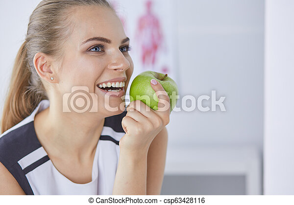Young beautiful smiling woman with a green apple in hands - csp63428116