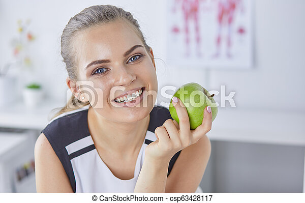 Young beautiful smiling woman with a green apple in hands - csp63428117
