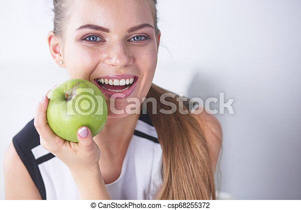 Young beautiful smiling woman with a green apple in hands - csp68255372
