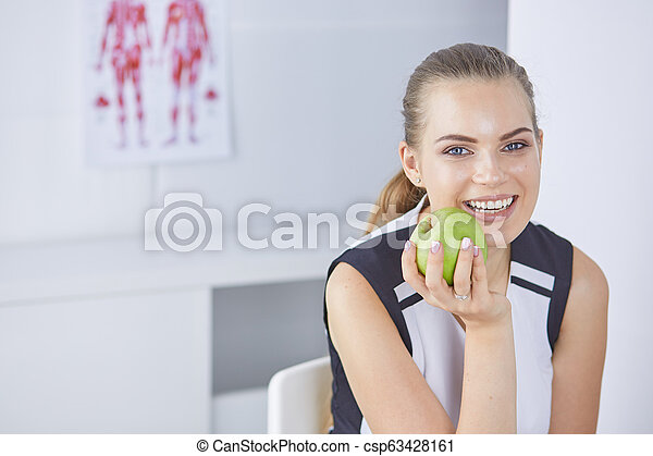 Young beautiful smiling woman with a green apple in hands - csp63428161