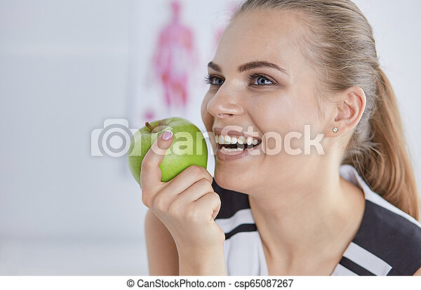 Young beautiful smiling woman with a green apple in hands - csp65087267