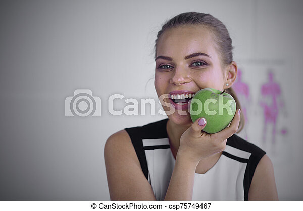 Young beautiful smiling woman with a green apple in hands - csp75749467