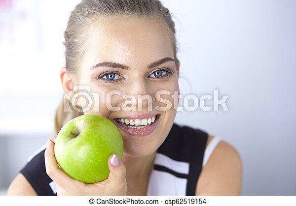 Young beautiful smiling woman with a green apple in hands - csp62519154