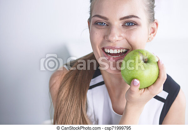 Young beautiful smiling woman with a green apple in hands - csp71999795