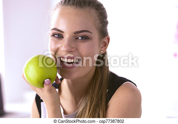 Young beautiful smiling woman with a green apple in hands - csp77387802