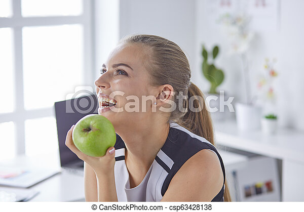Young beautiful smiling woman with a green apple in hands - csp63428138